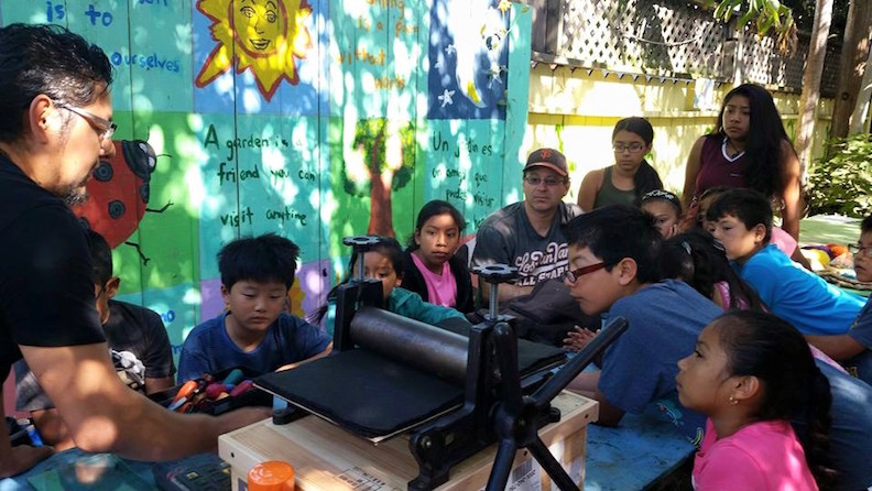 Jose Cruz screenprinting with children in Jardín Secreto.jpg