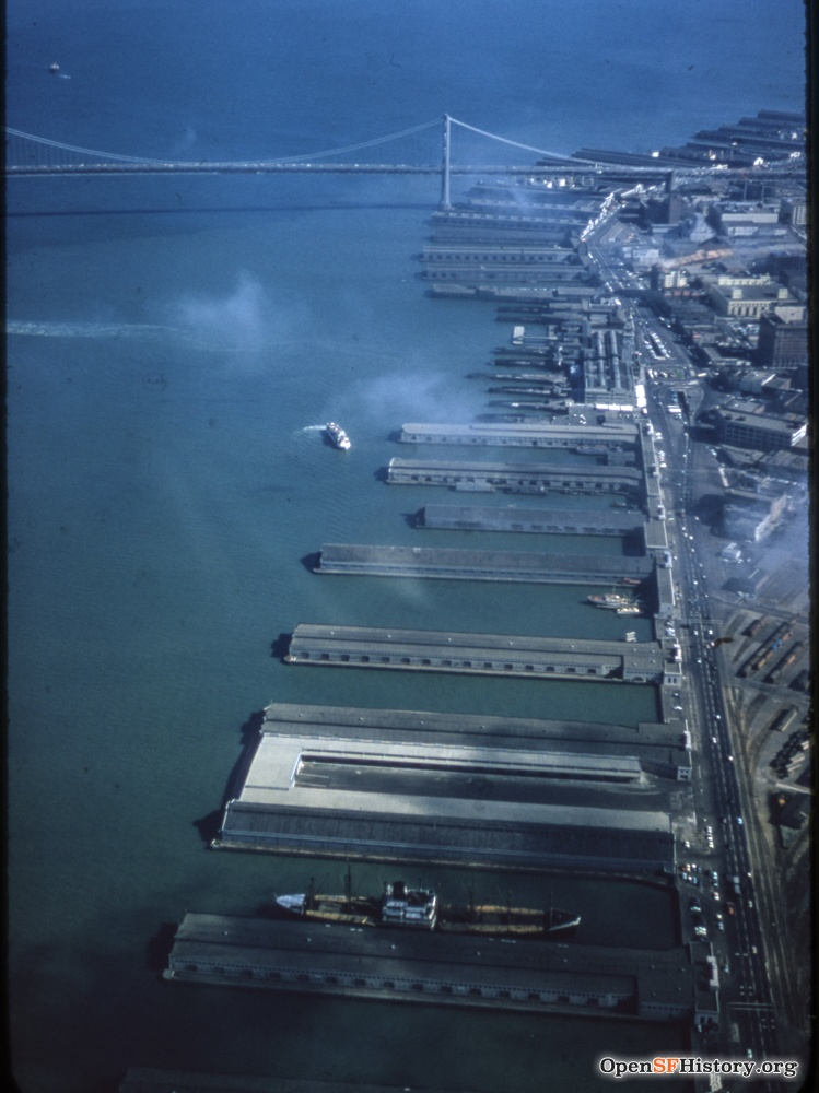 C1955 Aerial view looking south toward Bay Bridge, Belt Line Railroad yard at lower right. Ferry Building with vehicle underpass in front wnp25.2056.jpg