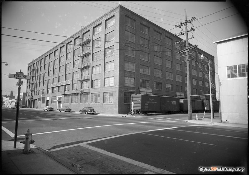 C 1955 View toward Northeast Corner of 15th and Folsom. Woolworth Company warehouse with railroad boxcars on 15th, presently occupied by the University of California San Francisco Mission Center. wnp100.00107.jpg